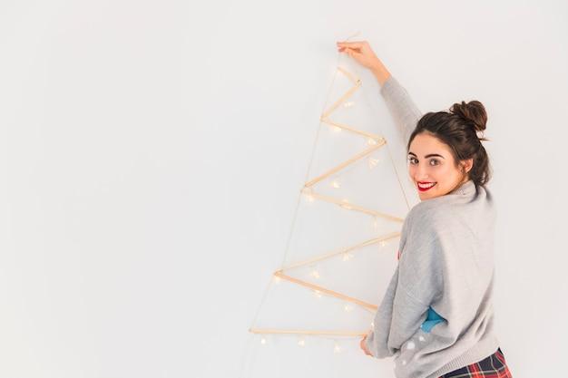 Frau, die hölzernen weihnachtsbaum an der wand hängt