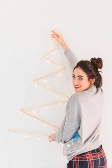Frau, die hölzernen weihnachtsbaum hängt