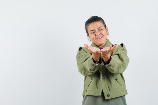 Frau, die hohlen hände in jacke, t-shirt streckt und friedlich aussieht