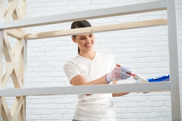 Frau, die holzplanke in der weißen farbe mit pinsel malt