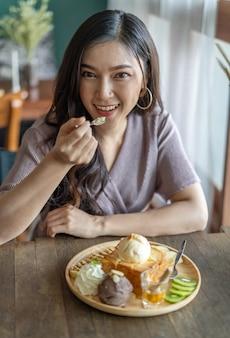 Frau, die honigtoast, süßspeise im café isst