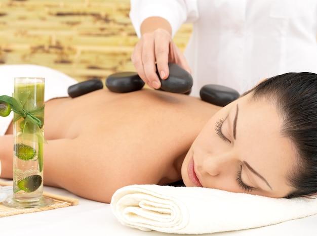 Frau, die hot stone spa massage des rückens im schönheitssalon hat