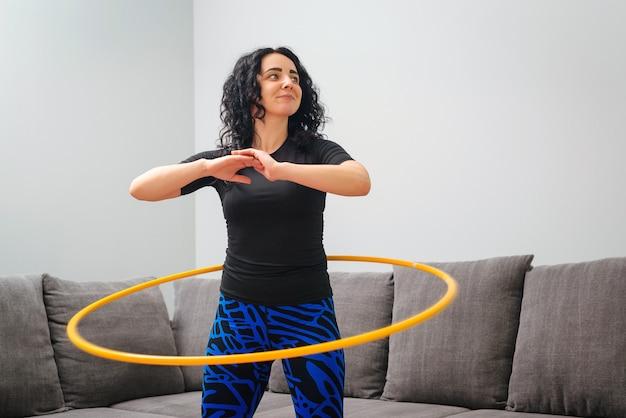Frau, die hula hoop dreht. mädchen trainieren zu hause. gesunder sportlicher lebensstil.