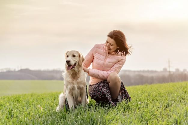 Frau, die hund draußen streichelt
