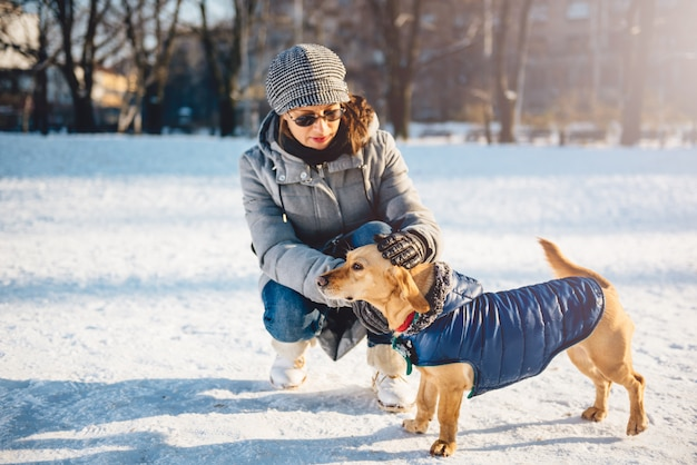 Frau, die hund im schnee streichelt