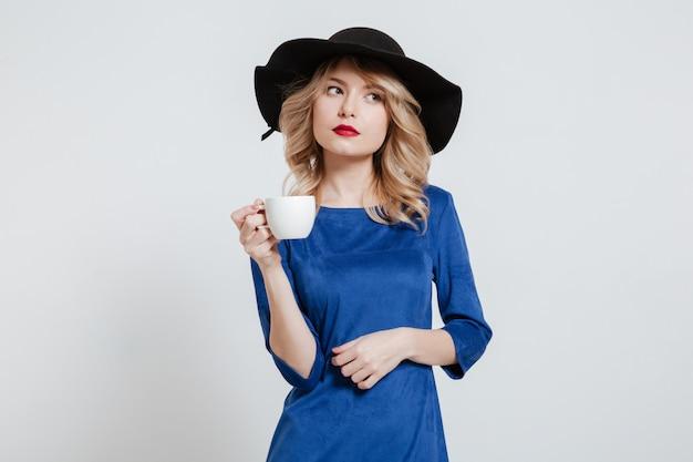 Frau, die hut hält tasse kaffee hält