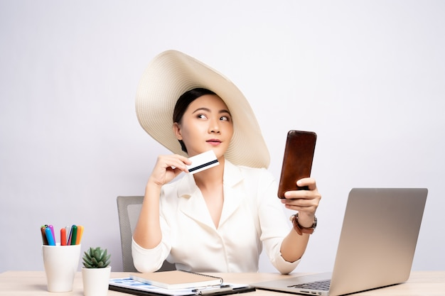 Frau, die hut trägt, verwendet smartphone und kreditkarte im büro lokalisiert über hintergrund