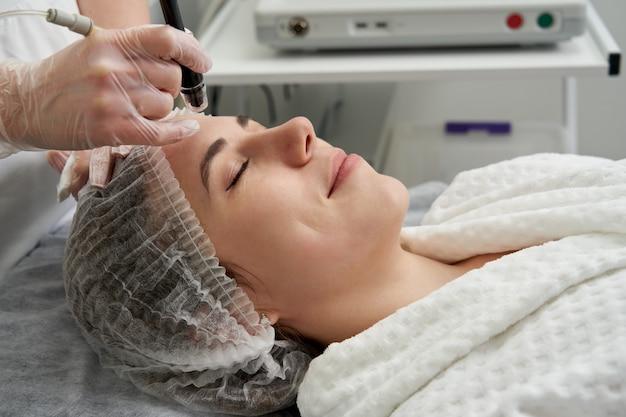 Frau, die hydro hydrodermabrasion peeling-behandlung im gesicht bei cosmetic beauty spa clinic erhält. hydra