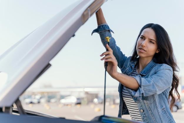 Frau, die ihr auto betrachtet, um ein problem zu lösen