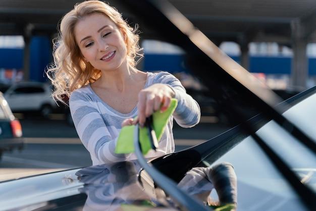 Frau, die ihr auto draußen putzt