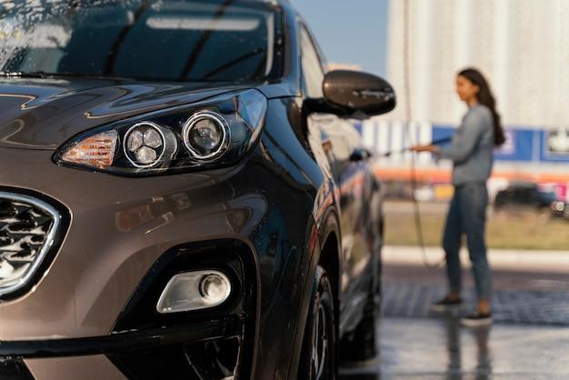 Frau, die ihr auto draußen wäscht