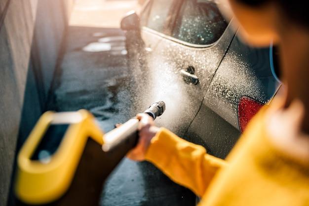 Frau, die ihr auto mit hochdruckreiniger wäscht