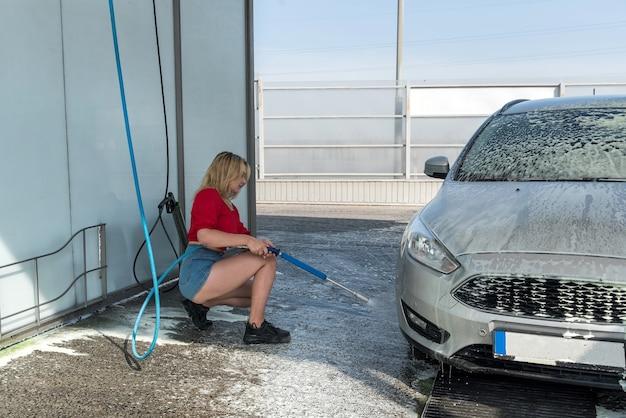 Frau, die ihr auto mit wasserstrahl mit schaum auf autowaschanlage säubert
