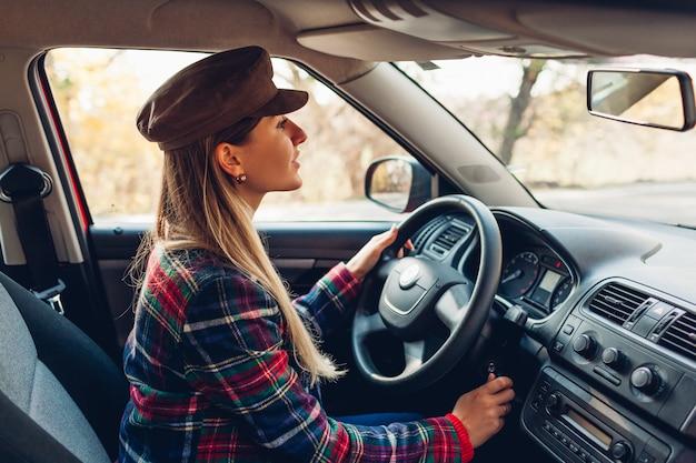 Frau, die ihr auto startet. junger fahrer fügt schlüssel in die zündung ein, die bereit ist zu gehen. der besitzer schaltet sich automatisch ein