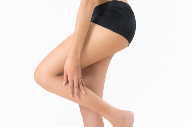 Frau, die ihr bein mit dem massieren des schienbeins und des kalbs in den schmerzbereichen lokalisiert auf weißem hintergrund hält