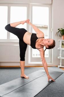 Frau, die ihr bein yoga zu hause konzept streckt