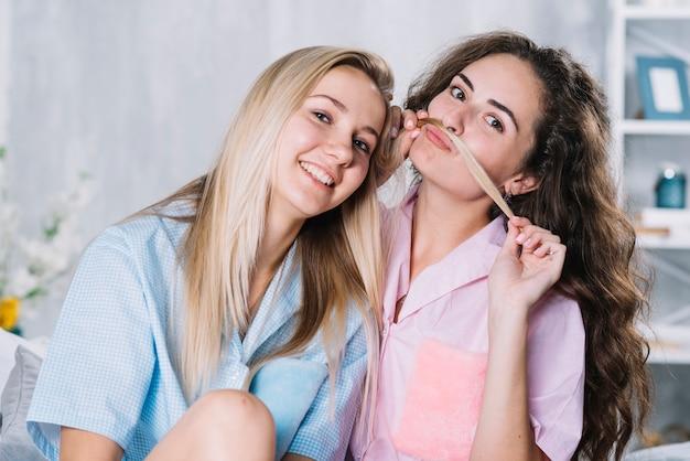 Frau, die ihr das haar der lächelnden freundin verwendet, um gefälschten schnurrbart zu machen