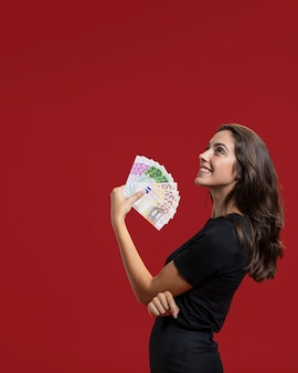 Frau, die ihr einkaufsgeld mit kopienraum zeigt