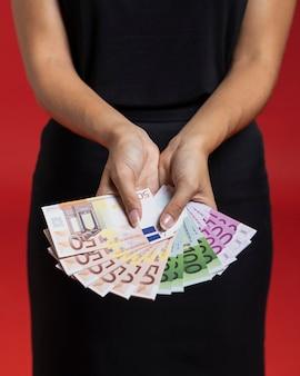 Frau, die ihr einkaufsgeld zeigt