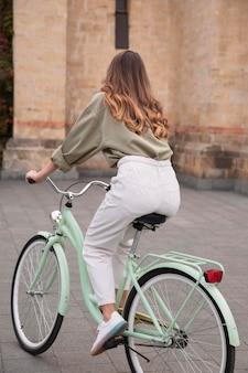 Frau, die ihr fahrrad draußen in der stadt reitet
