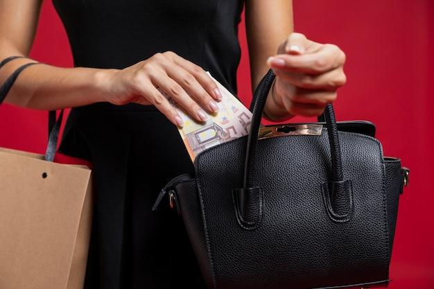 Frau, die ihr geld in ihren geldbeutel einsetzt