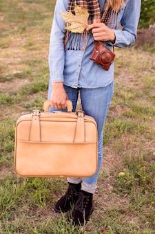 Frau, die ihr gepäck für das reisen hält