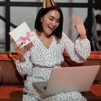 Frau, die ihr geschenk zeigt, während video-chat auf einer silvesterparty