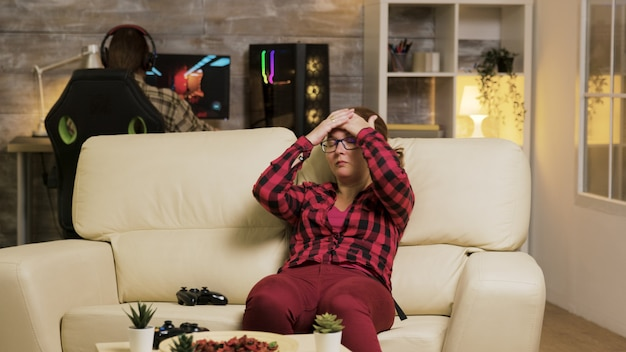 Frau, die ihr gesicht bedeckt, nachdem sie einen wettbewerb von videospielen verloren hat, während sie auf der couch im wohnzimmer sitzt. entspannter freund im hintergrund.