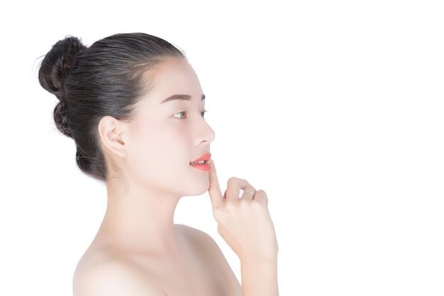Frau, die ihr gesicht, cosmetology, schönheit und badekurort, während lokalisiert auf weißem hintergrund berührt.
