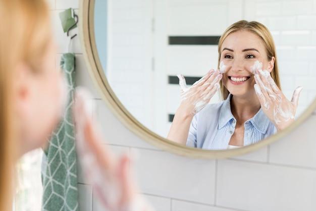 Frau, die ihr gesicht im badezimmerspiegel wäscht