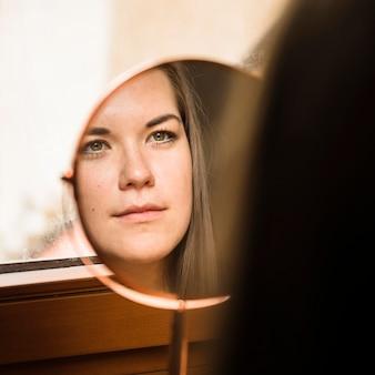 Frau, die ihr gesicht im spiegel betrachtet
