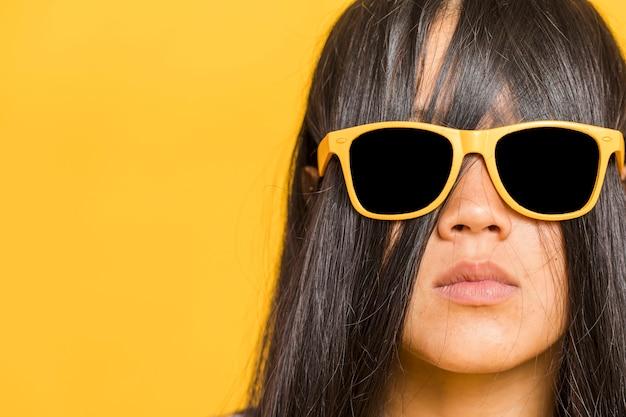 Frau, die ihr gesicht mit dem haar und sonnenbrille bedeckt