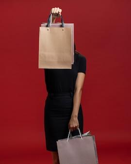 Frau, die ihr gesicht mit einer einkaufstasche bedeckt
