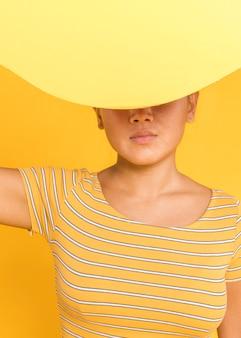 Frau, die ihr gesicht mit gelber karte bedeckt