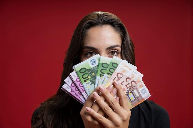Frau, die ihr gesicht mit geld bedeckt