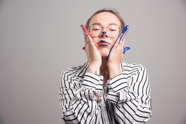 Frau, die ihr gesicht mit ihren farbenhänden auf grauem hintergrund berührt