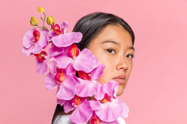 Frau, die ihr gesicht mit orchidee bedeckt und kamera betrachtet