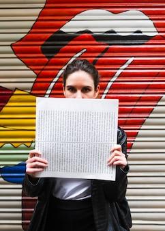 Frau, die ihr gesicht mit papier bedeckt