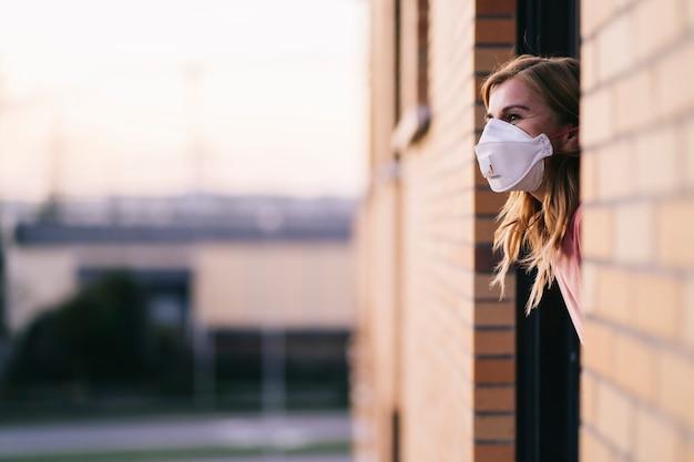 Frau, die ihr gesicht mit schutzmaske bedeckt