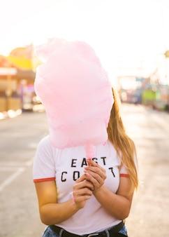 Frau, die ihr gesicht vor rosa süßigkeitsglasschlacke versteckt