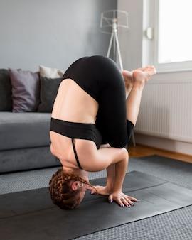 Frau, die ihr gewicht auf yogamatte hält