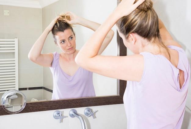 Frau, die ihr haar betrachtet spiegel im badezimmer bindet