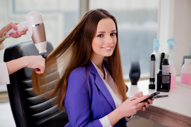 Frau, die ihr haar im schönheitssalon erledigt erhält
