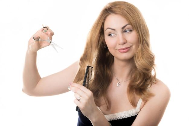 Frau, die ihr haar mit einer schere in ihren händen