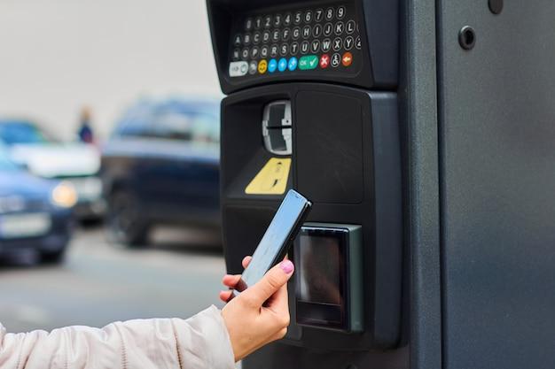 Frau, die ihr handy für die bezahlung des öffentlichen parkens durch nfc benutzt. kontaktloses zahlungssystem mit kopierplatz.