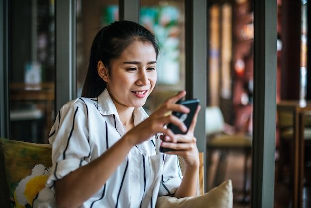Frau, die ihr intelligentes telefon am café sitzt und spielt