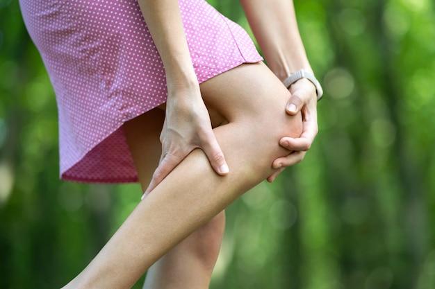 Frau, die ihr knie mit den händen hält, die gelenkschmerzen haben.