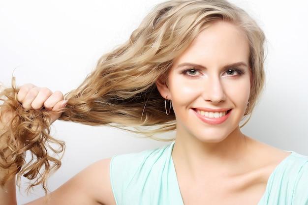 Frau, die ihr langes gelocktes gesundes haar hält