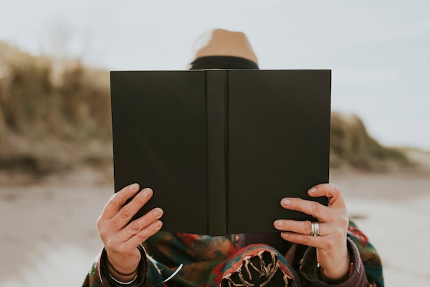 Frau, die ihr lesehobby im freien genießt