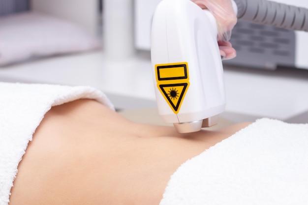 Frau, die ihr magenhaar vom weiblichen kosmetiker entfernen lässt. laser-epilationsbehandlung. nahansicht